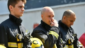 Firefighters pause to observe a minute's silence at the scene