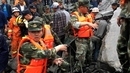 Chinese military police and rescue workers are seen at the site of a landslide in in Xinmo village