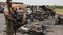 Soldiers stand guard beside burnt out vehicles at the scene where an oil tanker caught fire following an accident on a highway