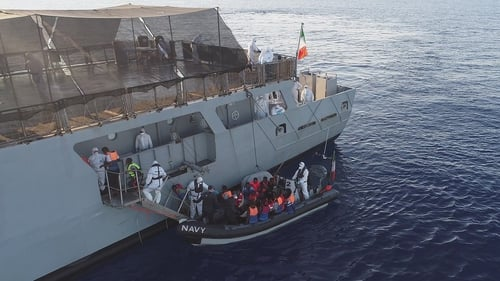 Rescued migrants are pictured being brought aboard the Irish Navy vessel