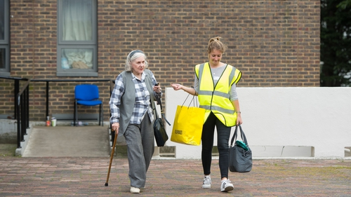 A council worker helps a resident leaving the Dorney tower on the Chalcots Estate, in London