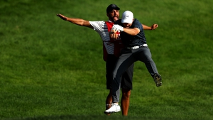 Spieth celebrates with caddie Michael Greller after chipping in for birdie from a bunker on the 18th green to win the Travelers Championship in a playoff against Daniel Berger