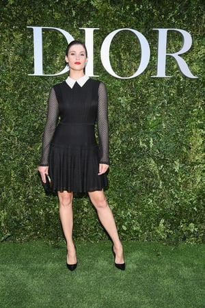 Gemma Arterton attends 'Christian Dior, couturier du reve'  in a simple black dress with fishnet sleeves and sharp white collar.