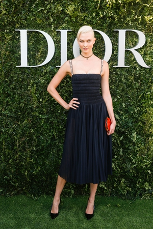 Model and dancer Karlie Kloss made a splash with platinum blonde hair and a strappy black cocktail dress from Dior's SS17 line.
