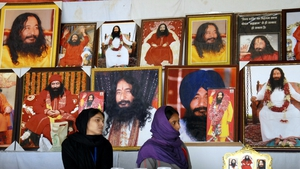 Followers of Ashutosh Maharaj sit in front of posters bearing his image during an event at his ashram