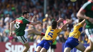 Mayo's Kevin McLoughlin scores a point despite the block attempt from Cian O'Dea of Clare
