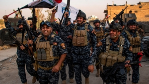 Members of the Iraqi federal police forces celebrate in the Old City of Mosul
