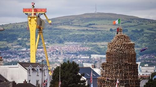 A tricolour flies from an unlit bonfire in Belfast