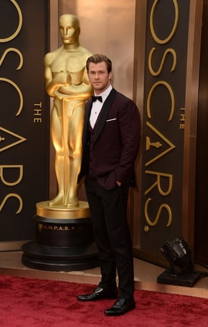 This David August burgundy tuxedo enhances Chris Hemsworth charm at the Oscars ceremony in 2014.