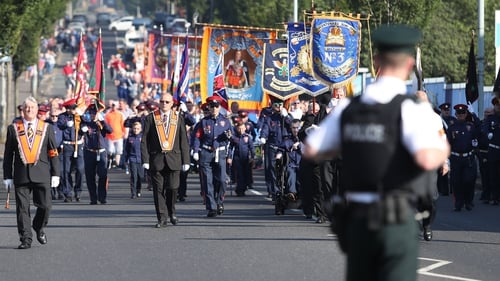 The Orange Order parade make its way past the nationalist Ardoyne area this morning