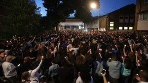 People attend a vigil to mark four weeks since the Grenfell Tower fire, at the memorial wall on Bramley Road, London