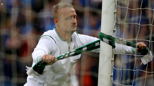 Leigh Griffiths ties a Celtic scarf around a goal post at Windsor Park
