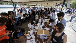 People wait to vote in the unofficial referendum in Caracas, Venezuela