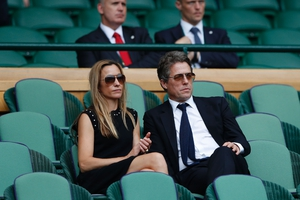 Hugh Grant and Anna Eberstein sit in the Royal box on Centre Court following the men's singles final match.