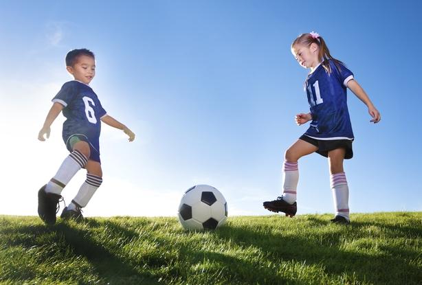 girl and boy playing football