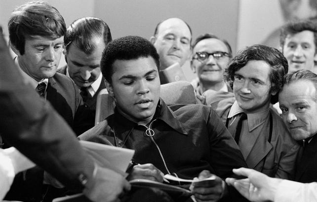 Muhammad Ali signs autographs