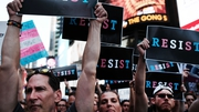 Dozens of protesters in Times Square show their anger at reinstatement of transgender  recruitment ban in military
