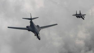 A US B1-B bomber (left) is escorted by a South Korean F-15K fighter as they fly over the Korean peninsula