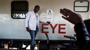 A doctor testing a patient's eye sight outside a mobile health train in South Africa