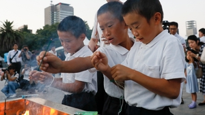 Children light incense sticks to offer prayers at the Hiroshima Peace Memorial Park