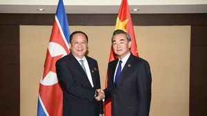 China's Foreign Minister Wang Yi (R) shakes hands with North Korea's Foreign Minister Ri Yong Ho (L) during their bilateral meeting