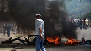 An anti-government activist stands near a burning barricade in Venezuela's third city, Valencia