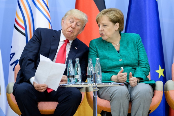 Lost in translation: Donald Trump and Angela Merkel compare notes. Photo: EPA/Michael Ukas