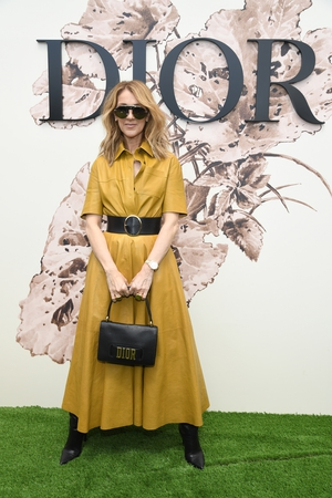 Celine Dion attended the Christian Dior Haute Couture 2017/18 show at Paris Fashion Week wearing a Dior yellow leather shirt dress with wide buckle belt and Dior handbag.