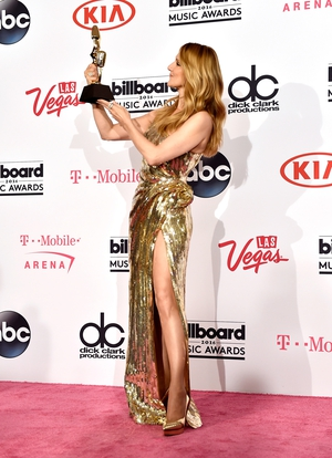 Dion poses with her Icon Award at the 2016 Billboard Music. She wore a stunning metallic number with thigh split with a pair of killer heels from Saint Laurent.