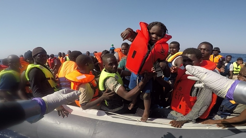 A small child is handed over to navy personnel during the rescue