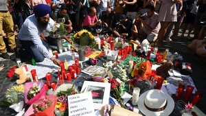 People stand next to flowers, candles and other items set up on the Las Ramblas boulevard as they pay tribute to the victims