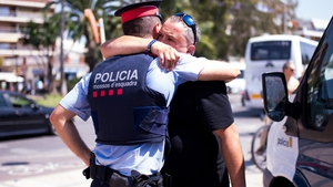 A man embraces a police officer near the area where five attackers were shot dead in Cambrils