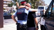 A man embraces a police officer at the place where the five terrorists were shot by police in Cambrils, Spain