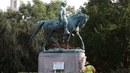 A homemade sign saying 'Heather Heyer Park' sits in front of the statue of General Robert E Lee in Charlottesville