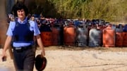 A policewoman walks past dozen of gas canisters in Alcanar