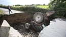 A man looks at a tractor which has fallen into a river after a road collapsed in Iskaheen, Co Donegal