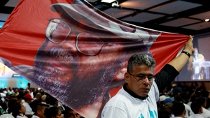 A man shows a flag with the picture of late FARC leader Guillermo Leon Saenz, during the National Congress