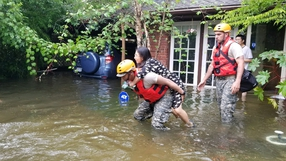 Texas National Guard help a woman our of her flooded home in Houston