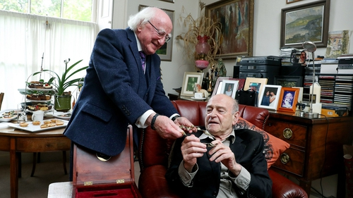 President Michael D Higgins presents playwright Tom Murphy with a gold Torc, in Dublin earlier today