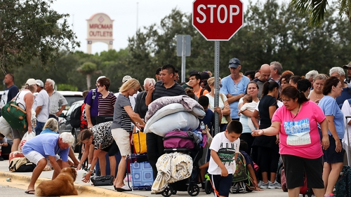 People wait in line to enter the Germain Arena that is serving as a shelter in Estero, Florida