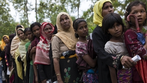 Rohingya refugee women queue for food rations after arriving from Myanmar on September 10, 2017 in Whaikhyang, Bangladesh