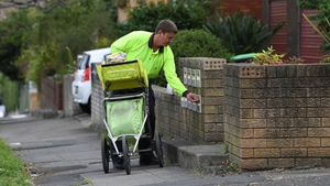 A postman delivers mail into boxes outside a residential building in Sydney as a contentious postal survey on same-sex marriage gets under way