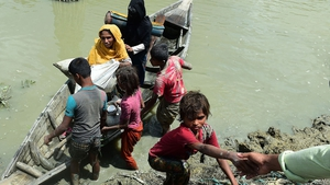 Local Bangladeshis help Rohingya Muslim refugees to disembark from a boat on the Bangladeshi side of Naf river