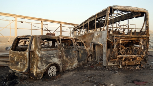 Burnt out vehicles after gunmen and suicide car bombers killed more than 70 people in two assaults