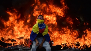 A Venezuelan opposition activist in front of a burning barricade during a demonstration against President Maduro
