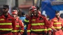 Rescuers leave a flattened multistory building after searching for survivors at the Roma neighbourhood in Mexico City