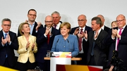 Angela Merkel (centre) and her CDU party members react to the exit polls this evening