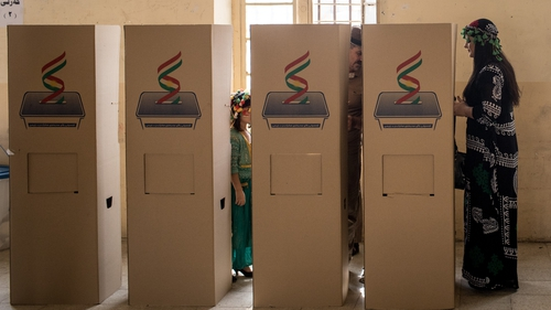 A woman waits to cast her referendum vote at a voting station in Kirkuk