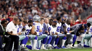 Members on the Dallas Cowboys kneel during the US national anthem
