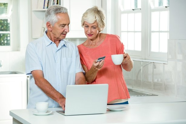 Senior couple with credit card while using laptop